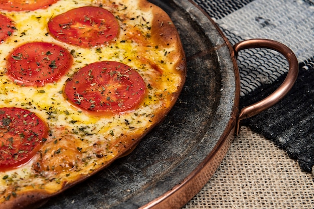 Pizza napolitana brasileira com queijo mussarela e fatias de tomate com orégano, vista de cima
