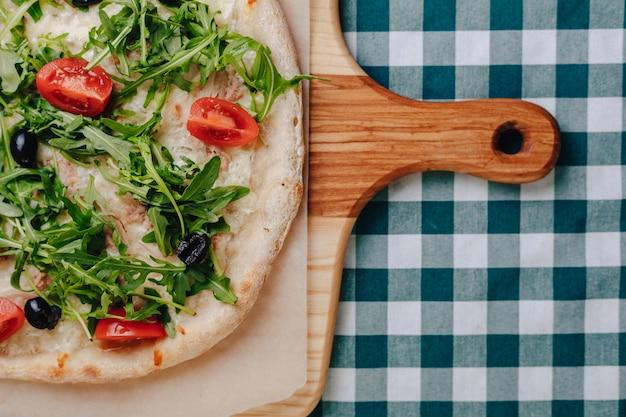 Pizza napolitana com atum, queijo, rúcula, manjericão, tomate, azeitonas, polvilhadas com queijo.