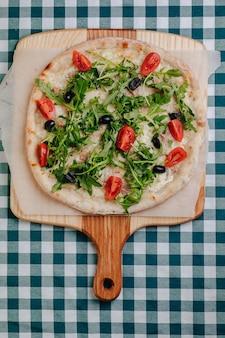 Pizza napolitana com atum, queijo, rúcula, manjericão, tomates, azeitonas, polvilhadas com queijo em uma tabela de madeira em uma toalha de mesa em uma pilha com um lugar para o texto.