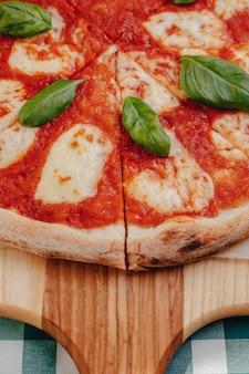 Pizza napolitana com presunto, queijo, rúcula, manjericão, tomate polvilhado com queijo em uma placa de madeira em uma toalha de mesa em uma célula