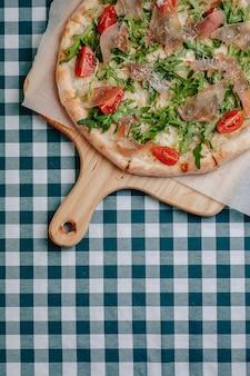 Pizza napolitana com salame, rúcula, tomate polvilhado com queijo em uma placa de madeira sobre uma toalha de mesa em uma célula com um lugar para texto