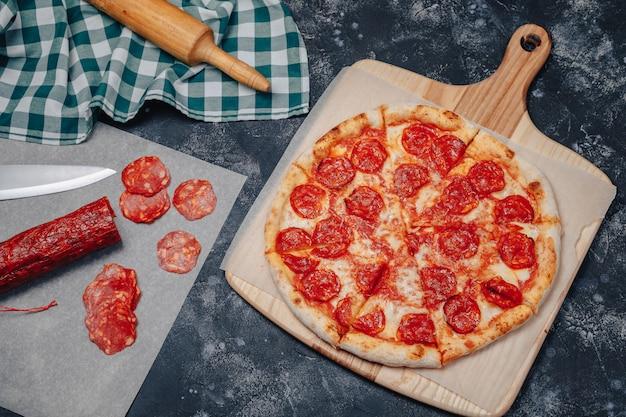 Pizza napolitana de dar água na boca em um quadro negro com vários ingredientes