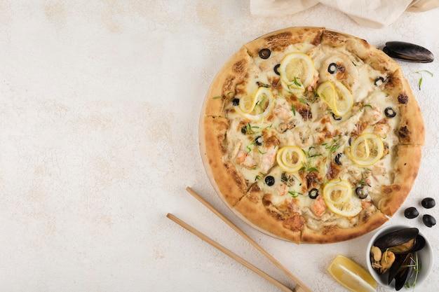 Pizza napolitano com frutos do mar, molho césar, salmão rosa, camarão, mexilhões, lulas, queijo mussarela, limão e azeitonas em um fundo claro. vista superior com um espaço de cópia para o texto.