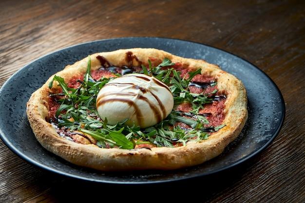 Pizza no forno a lenha com burrata, rúcula, molho vermelho e vinagre balsâmico. pizzette uma espécie de pizza italiana