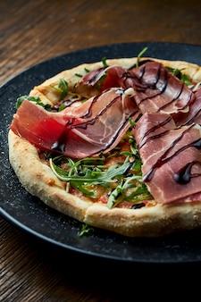 Pizza no forno a lenha com molho de jamon, rúcula e vermelho, servido em uma placa preta sobre um fundo de madeira. pizzette uma espécie de pizza italiana