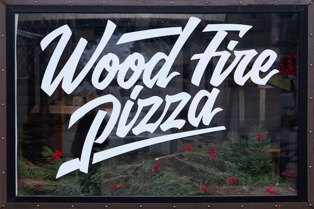 Pizza no forno a lenha, texto especial escrito em vitrine de vidro