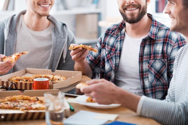 Pizza para trabalho produtivo. imagem recortada de três jovens felizes comendo pizza sentados à mesa juntos