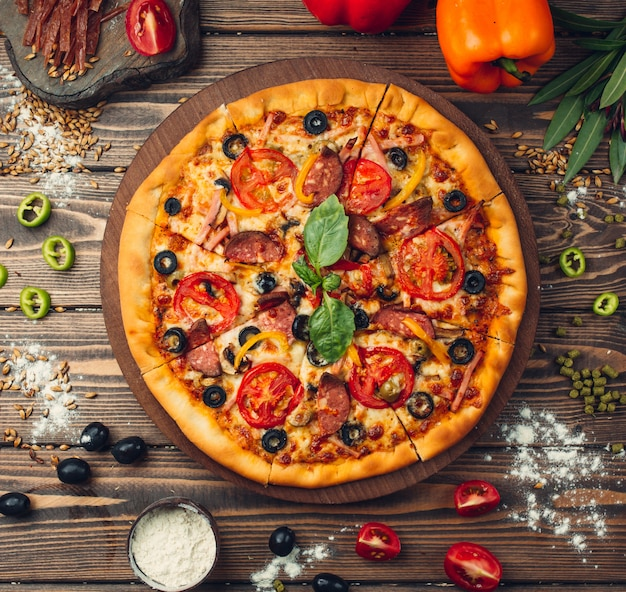 Pizza pizza cheia de tomates, salame e azeitonas