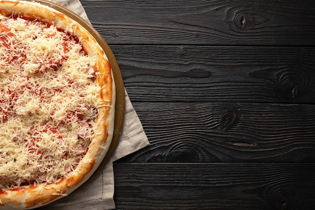 Pizza pronta para o forno em um fundo de madeira, lugar para texto, vista superior.