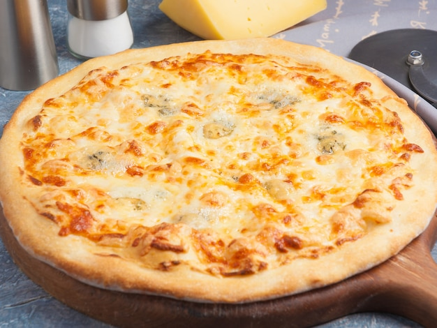 Pizza quatro queijos em uma placa de madeira