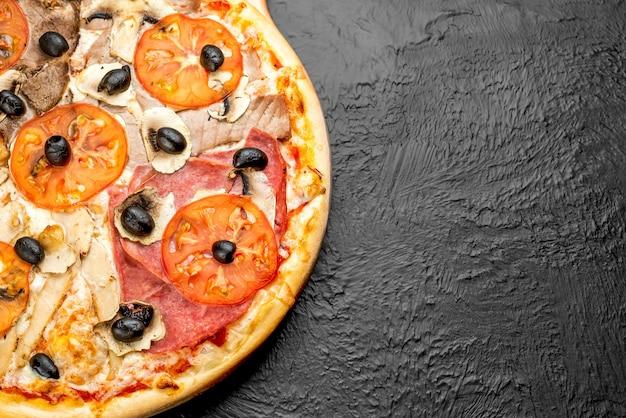 Pizza quatro sabores em fundo preto, à base de tomate com mussarela, vitela, presunto, azeitonas, atum, frango, cogumelos e tomate em uma bancada de madeira