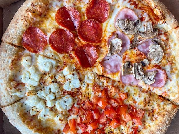 Pizza quatro temporadas em uma caixa. vista do topo