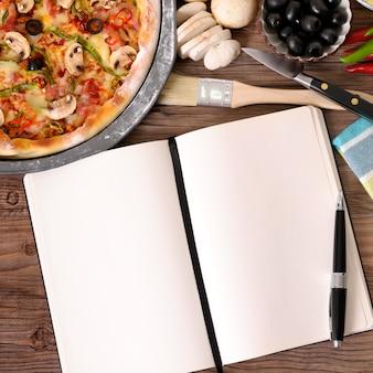Pizza recém-assada com livro de receitas