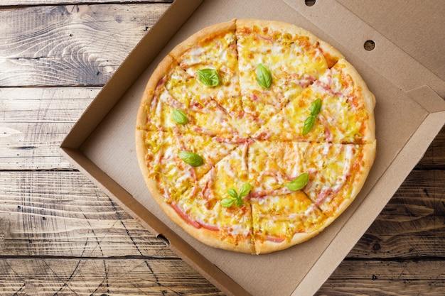 Pizza recém-assada em uma caixa de papelão em uma mesa de madeira.
