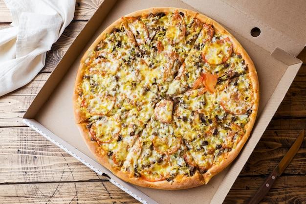 Pizza recentemente cozida em uma caixa de cartão em uma tabela de madeira.
