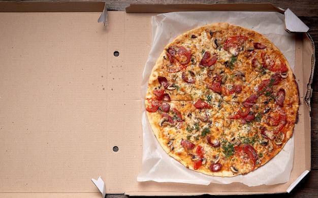 Pizza redonda assada com lingüiça defumada, cogumelos, tomate, queijo e endro em uma caixa de papelão aberta