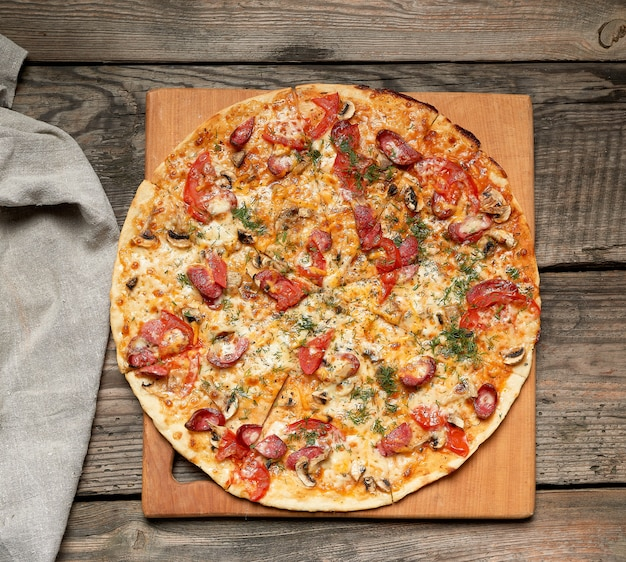 Pizza redonda assada com lingüiça defumada, cogumelos, tomate, queijo