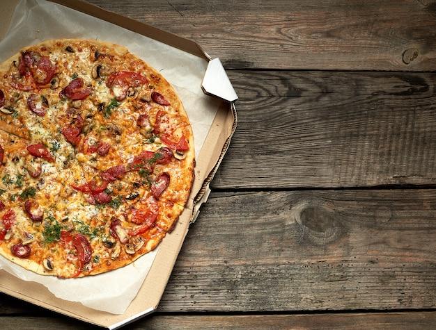 Pizza redonda assada com linguiças defumadas, cogumelos, tomate, queijo e endro em uma caixa de papelão aberta sobre uma mesa de madeira