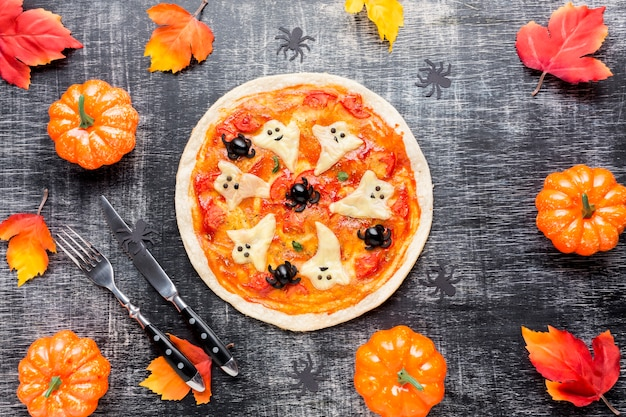 Pizza saborosa cercada por elementos de halloween