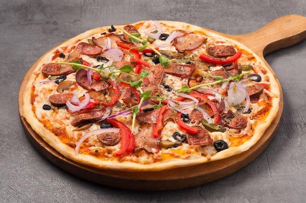 Pizza saborosa com bacon e salsichas de caça em um fundo cinza