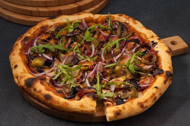 Pizza saborosa com bacon e vegetais em fundo escuro