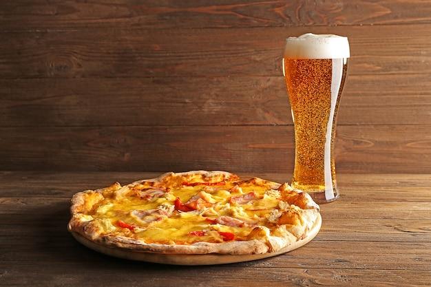 Pizza saborosa com cerveja na mesa de madeira