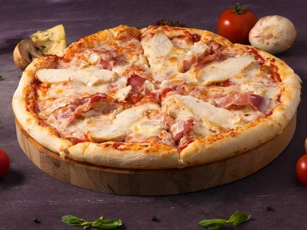 Pizza saborosa com frango, bacon e queijo em uma tábua de madeira
