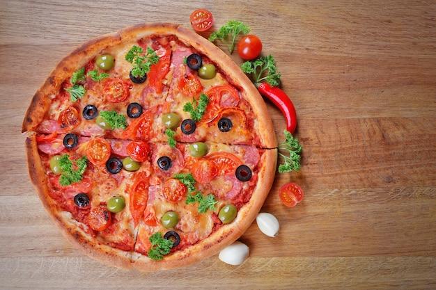 Pizza saborosa com linguiça e legumes na mesa de madeira