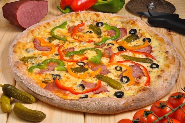 Pizza saborosa com picles de carne defumada, pimentão e queijo mussarela