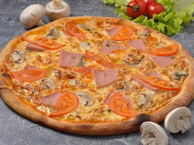 Pizza saborosa com presunto e cogumelos em fundo cinza