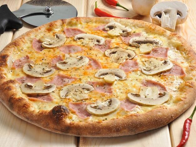 Pizza saborosa com presunto e cogumelos em uma mesa de madeira
