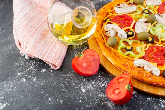Pizza saborosa de cogumelos com tomates vermelhos azeitonas verdes cogumelos com tomates frescos e azeite em toda a mesa escura pizza massa comida italiana