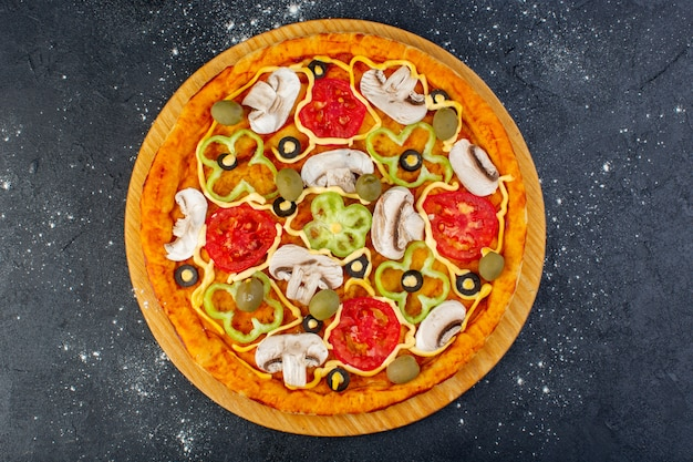 Pizza saborosa de cogumelos com tomates vermelhos, pimentões, azeitonas e cogumelos, tudo fatiado dentro da mesa cinza comida pizza italiana