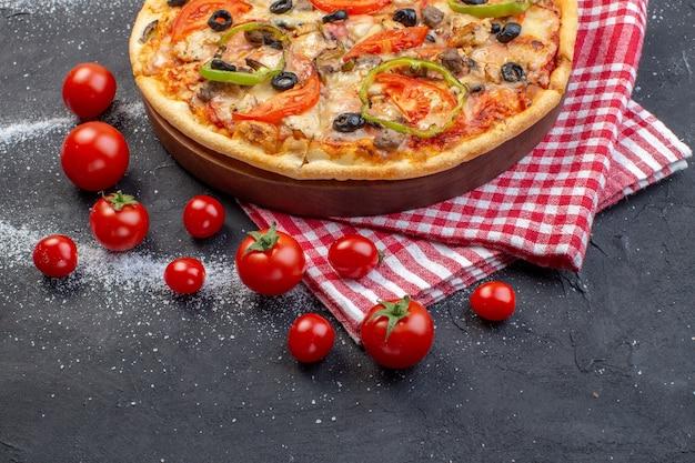Pizza saborosa de queijo com tomate vermelho em superfície escura de vista frontal