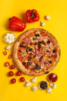 Pizza saborosa e ingredientes no amarelo