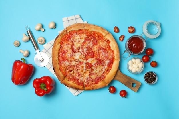 Pizza saborosa e ingredientes no azul