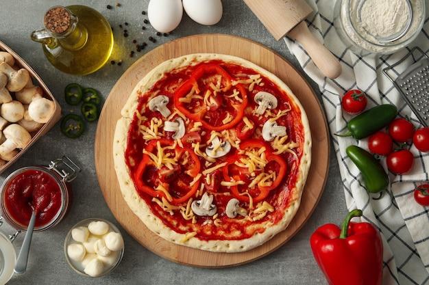 Pizza saborosa fresca com ingredientes na mesa cinza