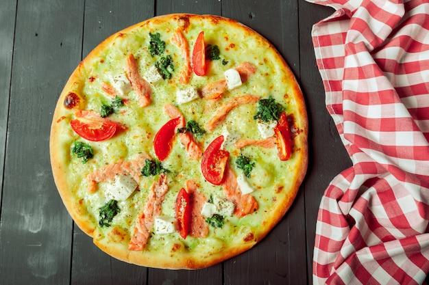 Pizza saborosa fresca em fundo de madeira