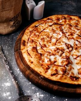 Pizza saborosa inteira com queijo na superfície cinza