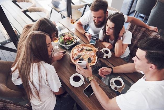 Pizza saborosa na mesa, com um grupo de jovens sorridentes descansando no bar.