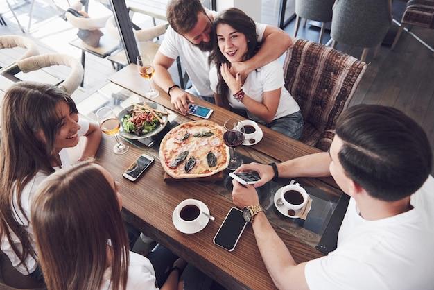 Pizza saborosa na mesa, com um grupo de jovens sorridentes descansando no pub