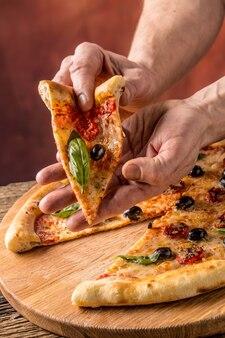Pizza. saborosa pizza italiana fresca servida na velha mesa de madeira. um pedaço de pizza na mão de um homem.