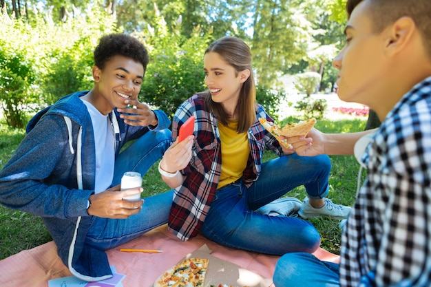 Pizza saborosa. três amigos sorridentes usando jeans comendo uma pizza saborosa juntos enquanto passam o tempo livre na natureza