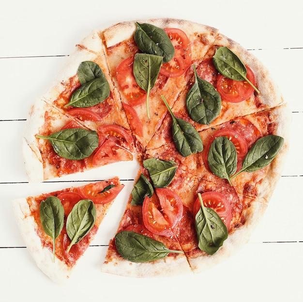 Pizza tradicional com fatias de tomate e folhas de manjericão