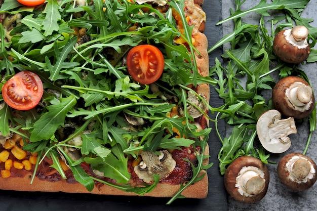 Pizza vegana com cogumelos e rúcula fresca. pizza quadrada com legumes, cogumelos e rúcula.