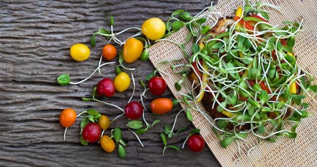 Pizza vegetariana caseira com broto de girassol e tomate cereja em um fundo de mesa de madeira