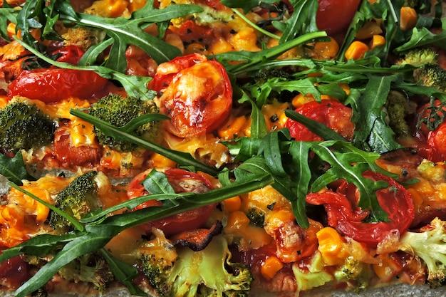 Pizza vegetariana caseira com legumes e rúcula fresca.