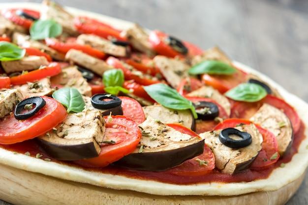 Pizza vegetariana com berinjela, tomate, azeitonas pretas, orégano e manjericão na mesa de madeira