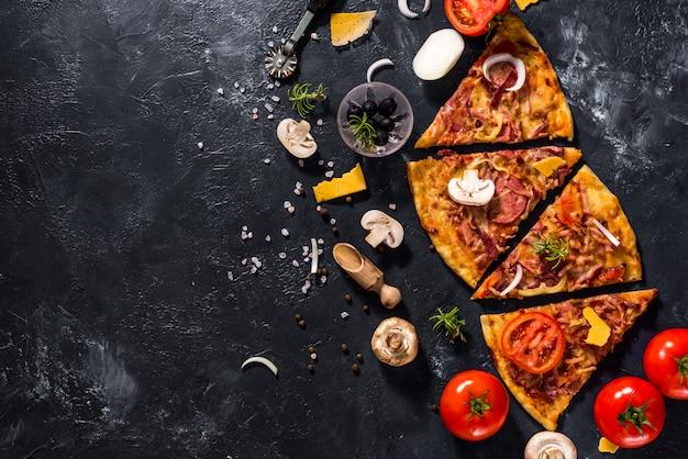 Pizza vegetariana fatiada italiana e ingredientes perto dele