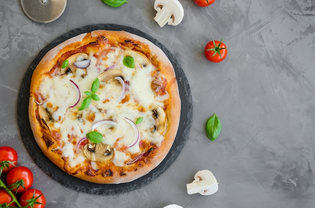 Pizza vegetariana italiana caseira com molho de tomate, cogumelos, queijo, cebola e manjericão em uma pedra em um fundo escuro.